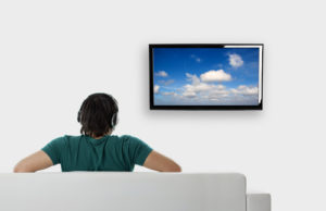 rear-view-from-a-young-man-seated-on-the-couch-watching-tv.tmb-large